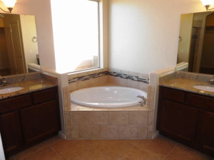 The garden tub in the master bathroom is flanked by two executive height vanities with granite countertops.